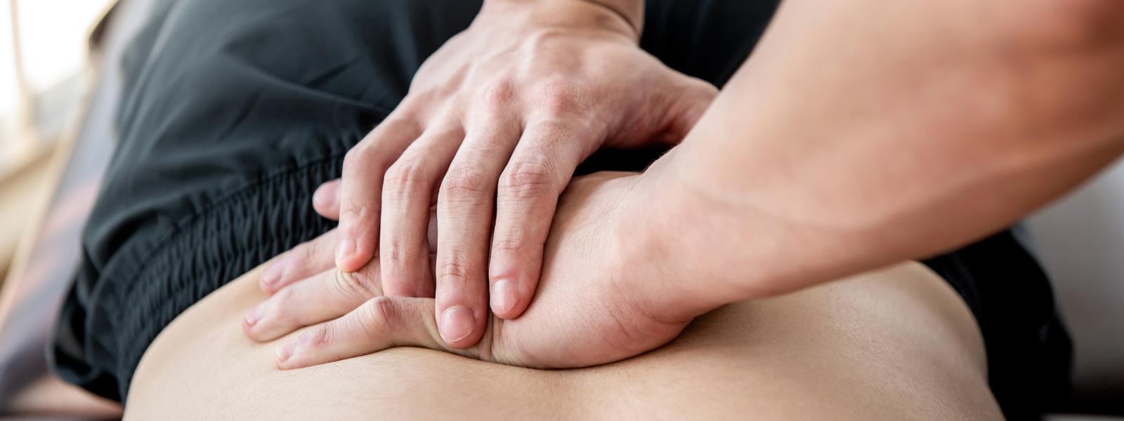 Hände die einen Rücken massieren